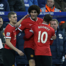 Manchester United's Marouane Fellaini, center, celebrates scoring his side's first goal with teammates Wayne Rooney and James Wilson, left, watched by Queens Park Rangers' manager Harry Redknapp, right, during the English Premier League soccer match betwe