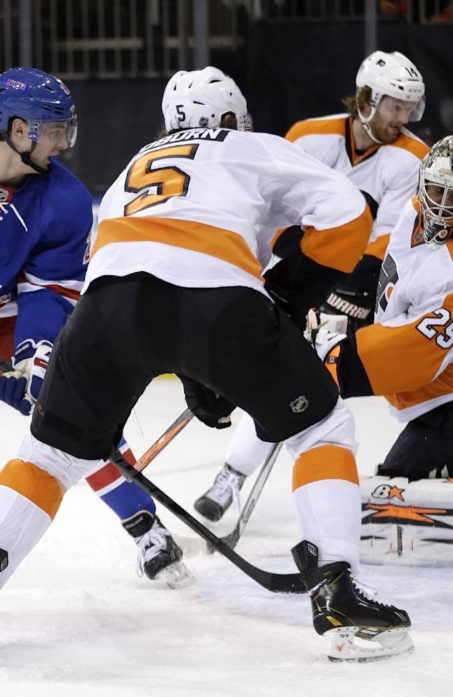 New York Rangers' Chris Kreider, left, watches as his shot gets past Philadelphia Flyers goalie Ray Emery, right, and Philadelphia Flyers' Braydon Coburn (5) during the second period of the NHL hockey game Sunday, Jan. 12, 2014, in New York