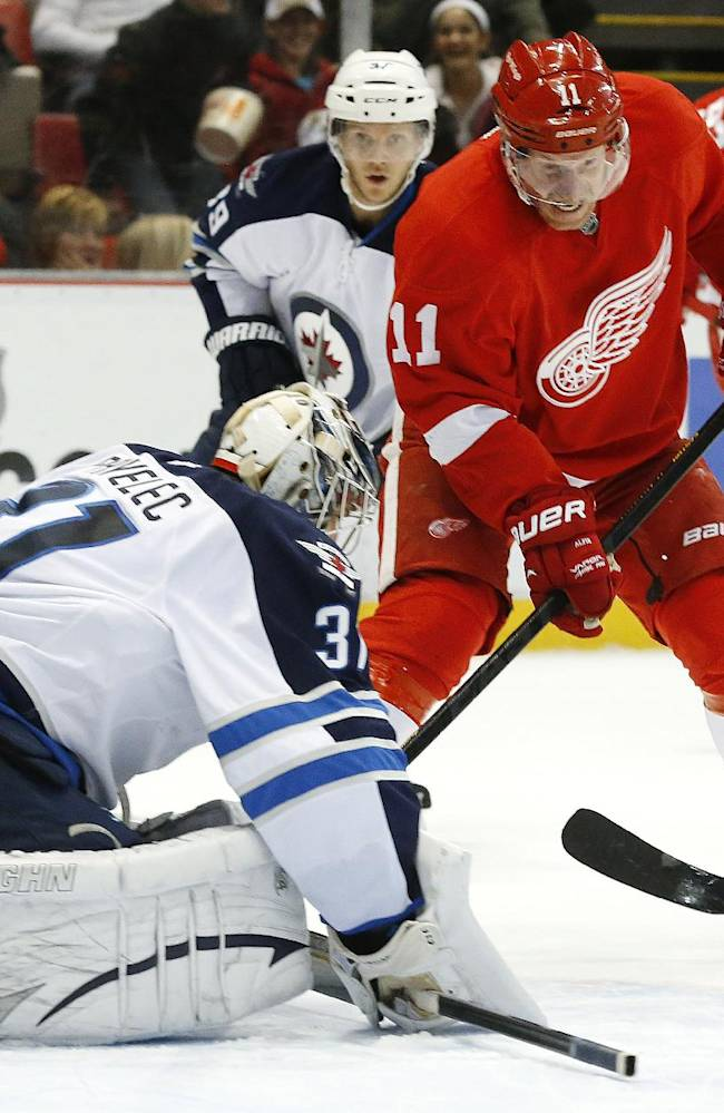 Winnipeg Jets goalie Ondrej Pavelec (31), of the Czech Republic, stops Detroit Red Wings right wing Daniel Alfredsson (11), of Sweden, shot during the second period of an NHL hockey game in Detroit, Tuesday, Nov. 12, 2013