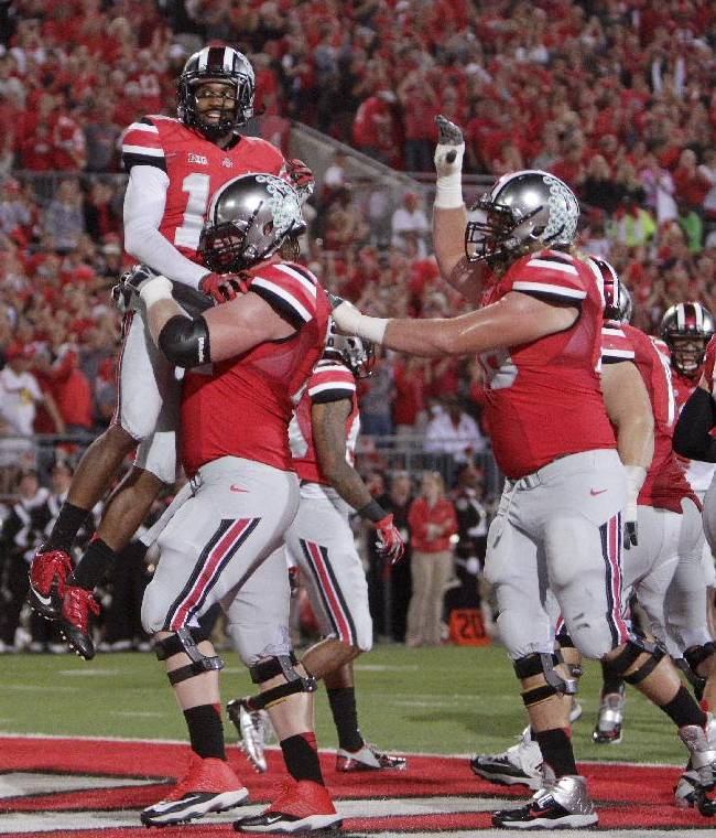 In this Sept. 28, 2013 file photo, Ohio State wide receiver Corey Brown, top, celebrates his touchdown against Wisconsin with teammates during the second quarter of an NCAA college football game in Columbus, Ohio. No. 4 Ohio State has completed a touchdown pass that has covered at least 20 yards at least 15 times, reflecting the Buckeyes' ability to throw deep passes more effectively