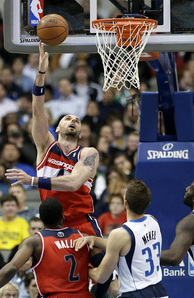 Washington Wizards' Marcin Gortat (4) goes up for shot as teammate John Wall (2) and Dallas Mavericks' Gal Mekel (33) and DeJuan Blair, right, watch in the second half of an NBA basketball game, Tuesday, Nov. 12, 2013, in Dallas. The Mavericks won 105-95
