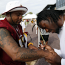 Charlie White, from Quinton, Va., gets an autograph from Washington Redskins quarterback Robert Griffin III after practice at the team's NFL football training facility, Sunday, July 27, 2014 in Richmond, Va. White has several Redskins players signatures t