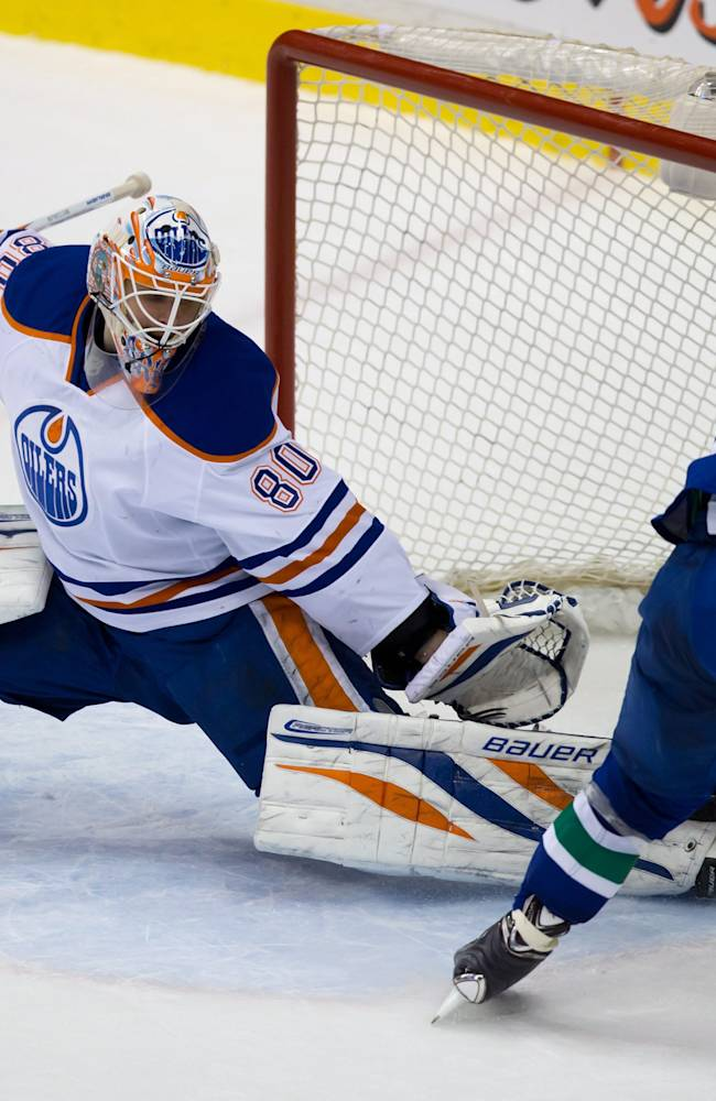 Edmonton Oilers' goalie Ilya Bryzgalov, left, of Russia, stops Vancouver Canucks' Chris Higgins during second period NHL hockey action in Vancouver, Canada, Sunday, Jan. 27, 2014
