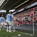 Manchester City's David Silva, centre left, celebrates with teammates after scoring his second goal against Liverpool during their English Premier League soccer match at Anfield Stadium, Liverpool, England, Sunday April 13, 2014