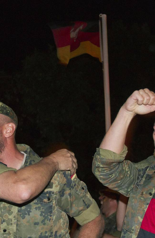 German soldiers serving in the NATO-led peacekeeping mission in Kosovo celebrate their team's World Cup victory against Argentina in Rio de Janeiro, Brazil, at the German military base in Prizren, Kosovo, early Monday, July 14, 2014. Germany won the final 1-0. (AP Photo/Visar Kryeziu)