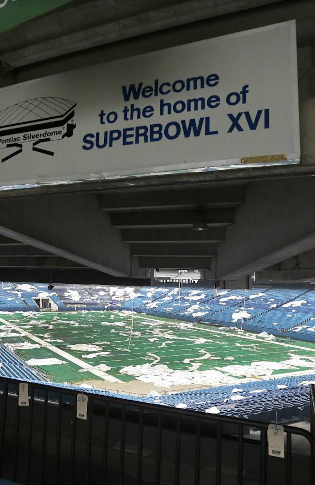 In this May 12, 2014 photo, the interior of the Pontiac Silverdome is seen in Pontiac, Mich. The 80,000-seat indoor stadium hosted the Super Bowl, the NBA finals, the World Cup, Wrestlemania and concerts by Elvis Presley, Led Zeppelin and the Rolling Stones. Nowadays, the venue is a shell of its former self with its roof in tatters and a lack of electrical power that has left the stadium's innards dark and mold-covered. The Silverdome's current owner is determined to cash in before it's too late, putting everything inside up for auction starting on Wednesday, May 21