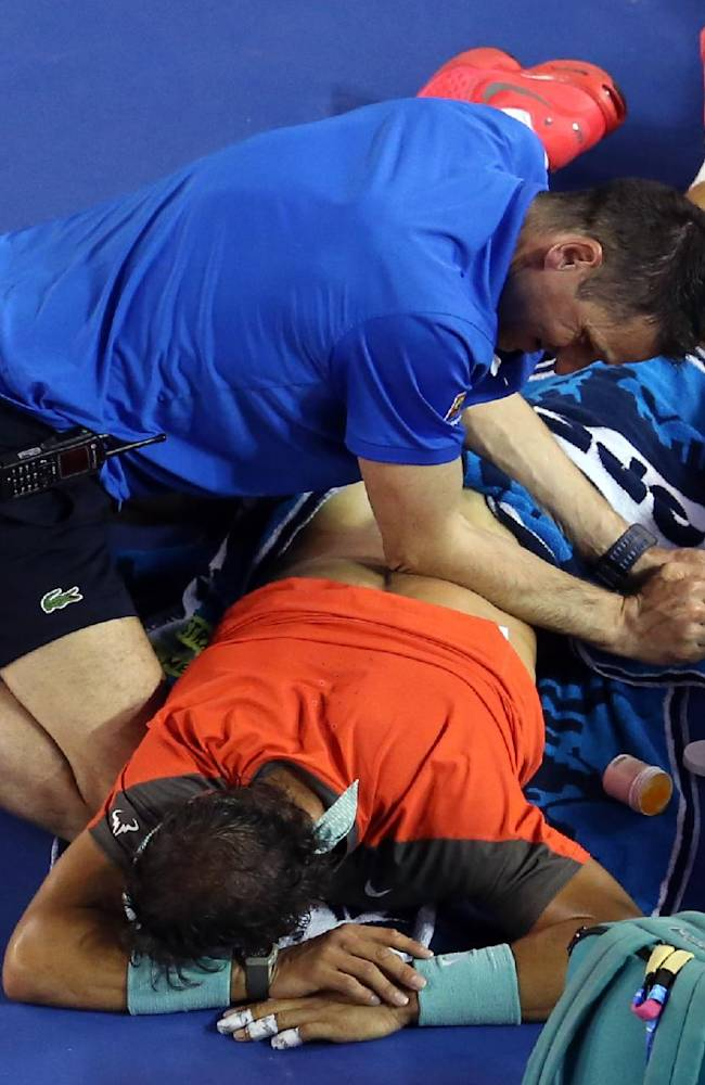 Rafael Nadal of Spain receives a medical treatment to his back during the men's singles final against Stanislas Wawrinka of Switzerland at the Australian Open tennis championship in Melbourne, Australia, Sunday, Jan. 26, 2014