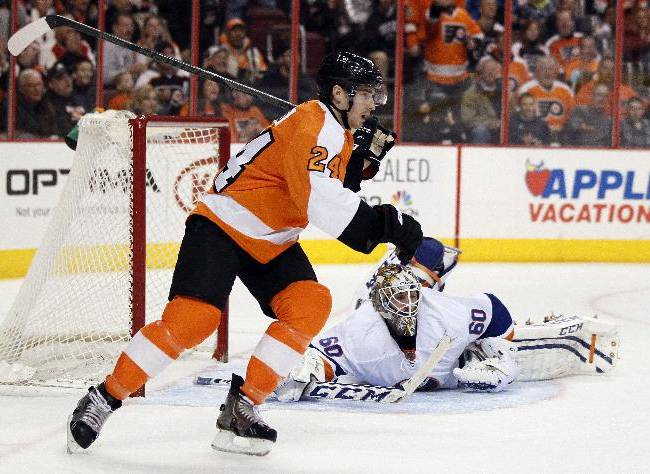 Philadelphia Flyers' Matt Read, left, skates past New York Islanders goalie Kevin Poulin during the second period of an NHL hockey game, Saturday, Jan. 18,  2014, in Philadelphia. Read went on to score an empty-net goal to seal the Flyers' 6-4 win