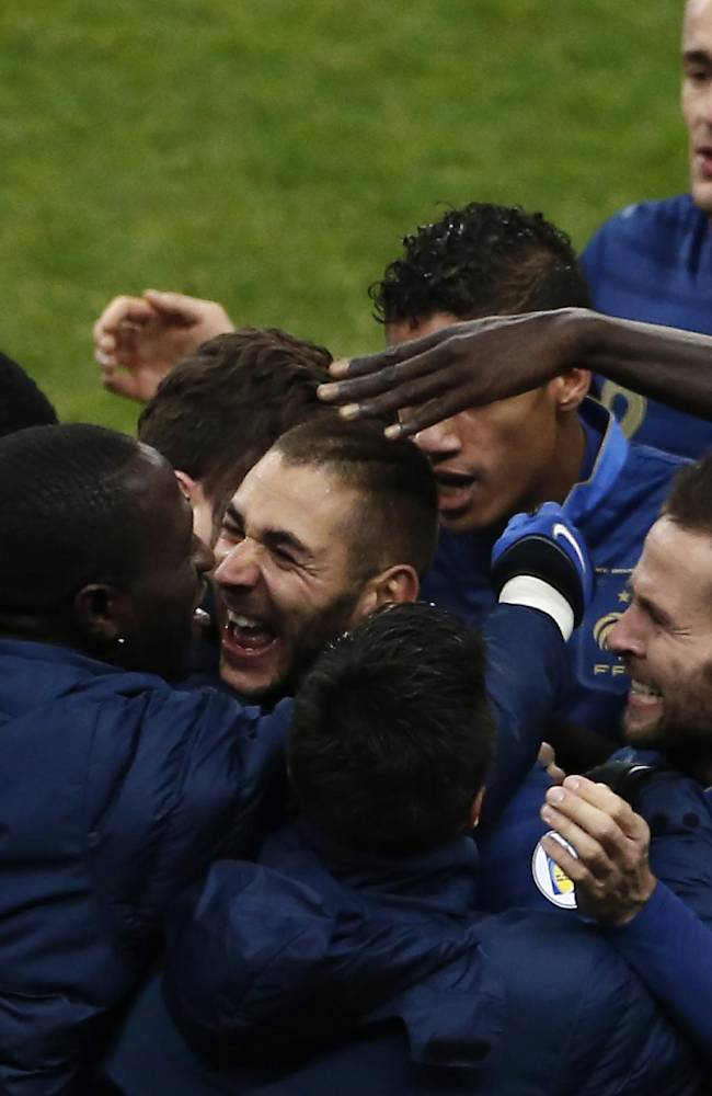France's Karim Benzema, center, celebrates with teammate after scoring during the World Cup qualifying playoff second-leg soccer match between France and Ukraine at Stade de France stadium, in Saint Denis, outside Paris, Tuesday, Nov. 19, 2013