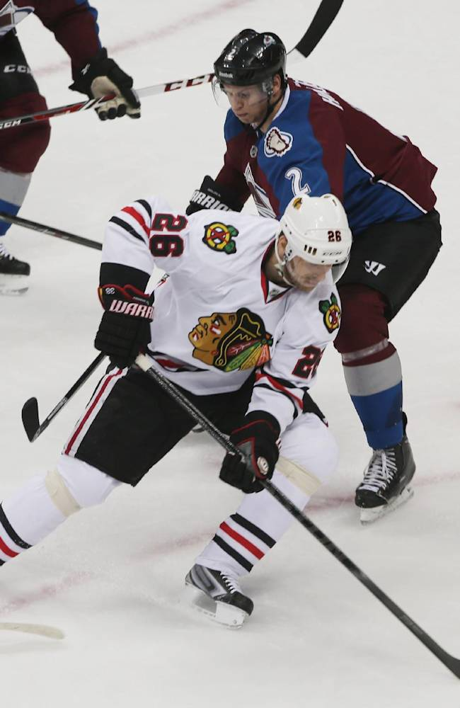 Chicago Blackhawks center Michal Handzus, front, of Slovakia, picks up a loose puck as Colorado Avalanche defenseman Nick Holden covers in the first period of an NHL hockey game in Denver on Wednesday, March 12, 2014