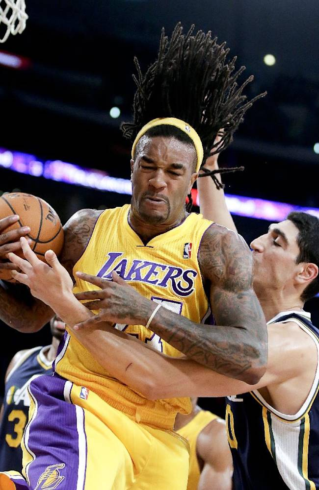 Los Angeles Lakers center Jordan Hill, left, fights over a rebound with Utah Jazz center Enes Kanter during the first half of a preseason NBA basketball game in Los Angeles, Tuesday, Oct. 22, 2013
