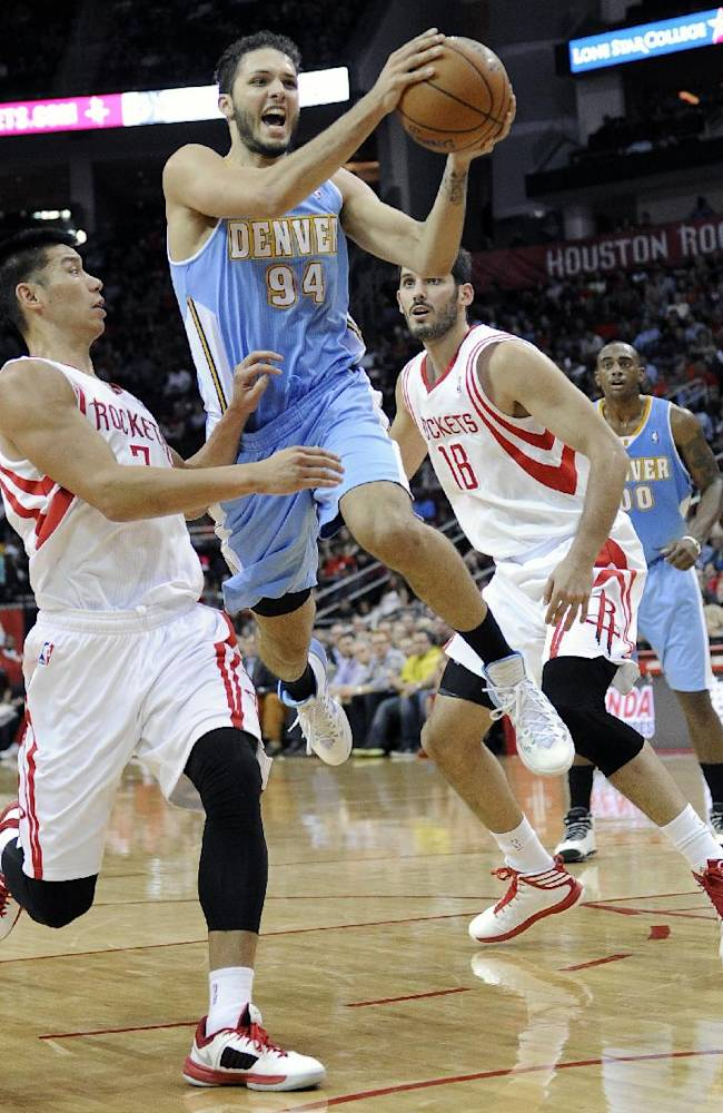 Denver Nuggets' Evan Fournier (94) goes to the basket between Houston Rockets Jeremy Lin, left, and Omri Casspi (18) in the first half of an NBA basketball game Saturday, Nov. 16, 2013, in Houston