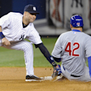 New York Yankees shortstop Derek Jeter, left, tags out Chicago Cubs' Anthony Rizzo who was attempting to steal second base during the fourth inning of Game 2 of an interleague baseball doubleheader on Wednesday, April 16, 2014, at Yankee Stadium in New Yo