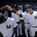 New York Yankees' designated hitter Alex Rodriguez high fives a teammate before a spring training baseball exhibition game against the Philadelphia Phillies, Wednesday, March 4, 2015, in Tampa, Fla. (AP Photo/Lynne Sladky)