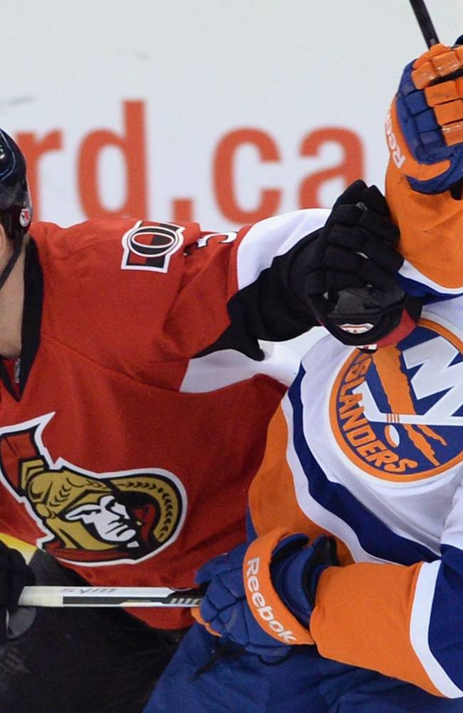 Ottawa Senators' Marc Methot pushes New York Islanders' Mike Halmo out of the way during the second period of an NHL hockey game in Ottawa, Ontario, on Wednesday, April 2, 2014