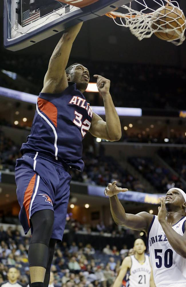 Atlanta Hawks' Mike Scott (32) dunks the ball over Memphis Grizzlies' Zach Randolph (50) in the first half of an NBA basketball game in Memphis, Tenn., Sunday, Jan. 12, 2014