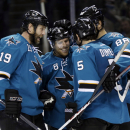San Jose Sharks' Joe Pavelski (8) is hugged by teammates after scoring against the Toronto Maple Leafs during the third period of an NHL hockey game Tuesday, March 11, 2014, in San Jose, Calif. San Jose won 6-2 The Associated Press