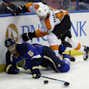 St. Louis Blues' Barret Jackman (5) reaches for a loose puck along side Philadelphia Flyers' Vincent Lecavalier during third period of an NHL hockey game Tuesday, April 1, 2014, in St. Louis. The Blues won 1-0 in a shootout The Associated Press