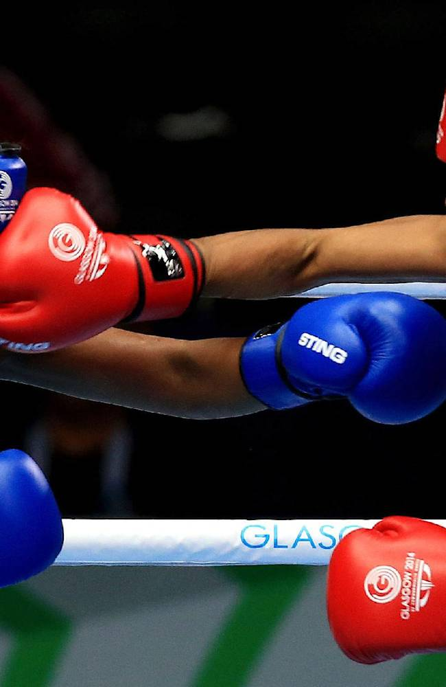Kiribati's Taoriba Biniati, left, fights Mauiritius Isabelle Ratna in the women's light 57-60 kg boxing bout during the 2014 Commonwealth Games in Glasgow, Scotland, Tuesday July 29, 2014