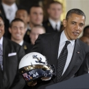 President Barack Obama holds a Navy football team helmet and explains why he won't put it on after presenting the Commander-in-Chief Trophy to the United States Naval Academy football team, Friday, April 12, 2013, in the East Room of the White House in Washington. Head coach Ken Niumatalolo watches at left. The helmet bears a