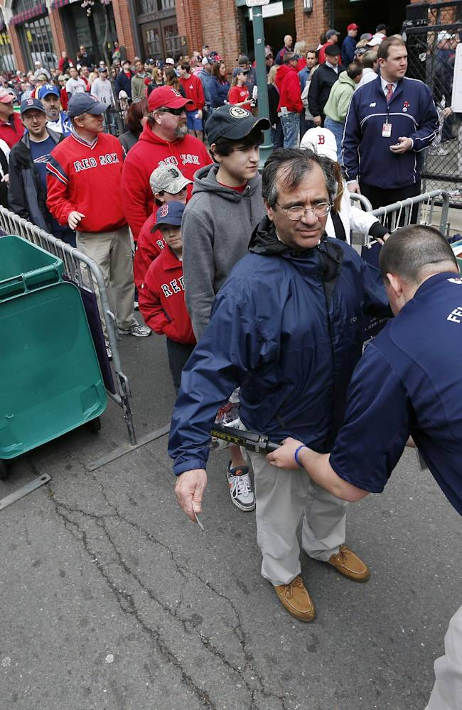 In this April 20, 2013 file photo, fans pass through a security checkpoint before entering Fenway Park for a baseball game between the Boston Red Sox and the Kansas City Royals in Boston. Baseball fans should expect to go through a metal detector to see their team play in 2014. MLB security director John Skinner says at a panel discussion at Harvard that the commissioner's office plans to recommend walkthrough metal detectors