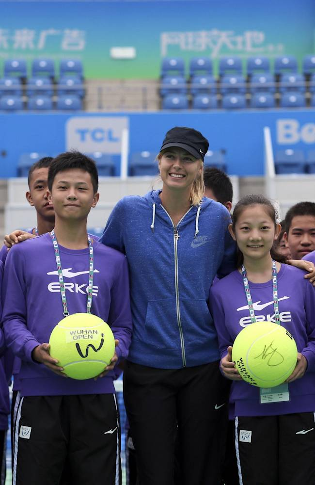 Maria Sharapova of Russia, center, poses for photographs with ball boys and girls holding autographed tennis balls during a promotional event ahead of the WTA Wuhan Open Tennis Tournament in Wuhan in central China's Hubei province Thursday, Sept. 18, 2014. The tournament will kick-off from Sept. 21 to 27, featuring World's Top 20 women players. (AP Photo)