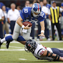 New York Giants quarterback Eli Manning (10) is tripped up for a sack by Houston Texans defensive end J.J. Watt (99) in the first quarter of an NFL football game, Sunday, Sept. 21, 2014, in East Rutherford, N.J The Associated Press