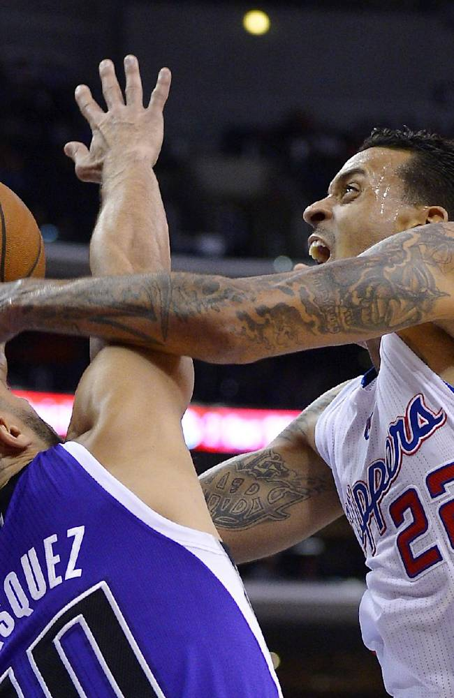 Los Angeles Clippers small forward Matt Barnes, right, puts up a shot as Sacramento Kings point guard Greivis Vasquez defends during the first half of their NBA basketball game, Friday, Oct. 25, 2013, in Los Angeles