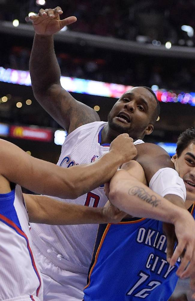 Los Angeles Clippers forward Jared Dudley, left, forward Glen Davis, center, and Oklahoma City Thunder center Steven Adams, battle for a rebound in the second half of Game 3 of the Western Conference semifinal NBA basketball playoff series, Friday, May 9, 2014, in Los Angeles. The Thunder won 118-112