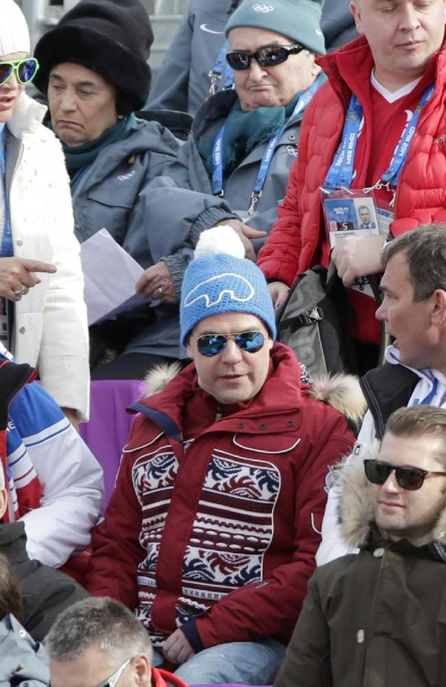 Russian Prime Minister Dmitry Medvedev, center, speaks to other spectators at the Alpine ski venue during the men's downhill ay the Sochi 2014 Winter Olympics, Sunday, Feb. 9, 2014, in Krasnaya Polyana, Russia