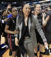South Carolina head coach Dawn Staley, center, Markeshia Grant, left, and and Courtney Newton, right, celebrate their 59-55 win over Georgia in an NCAA college basketball game at the women's Southeastern Conference tournament on Friday, March 2, 2012, in Nashville, Tenn. (AP Photo/Mark Humphrey)