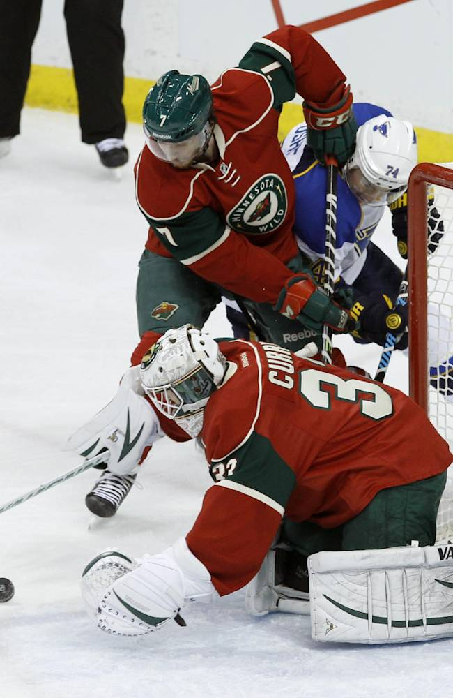 Minnesota Wild goalie John Curry (33) dives on the puck after deflecting a shot by St. Louis Blues right wing T.J. Oshie (74) as Wild defenseman Jonathon Blum (7) holds Oshie away from the rebound during the first period of an NHL hockey game in St. Paul, Minn., Thursday, April 10, 2014. The Wild won 4-2