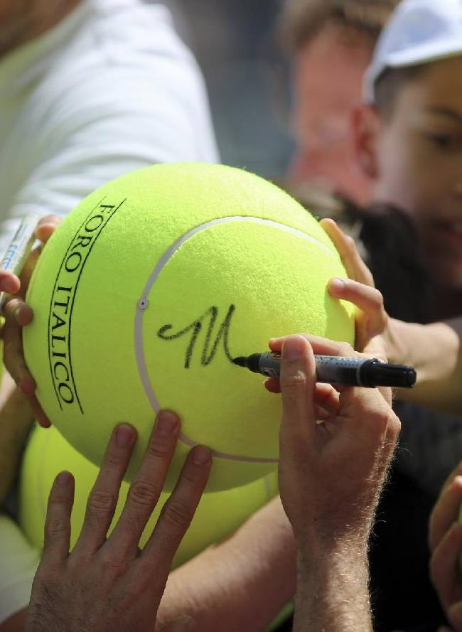 Germany's Tommy Haas signs autographs after winning his match against Switzerland's Stanislas Wawrinka at the Italian open tennis tournament in Rome, Thursday, May 15, 2014