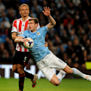 Manchester City's Edin Dzeko is tackled by Sunderland's Wes Brown during the English Premier League soccer match between Manchester City and Sunderland at The Etihad Stadium, Manchester, England, Wednesday, April 16, 2014. (AP Photo/Rui Vieira)