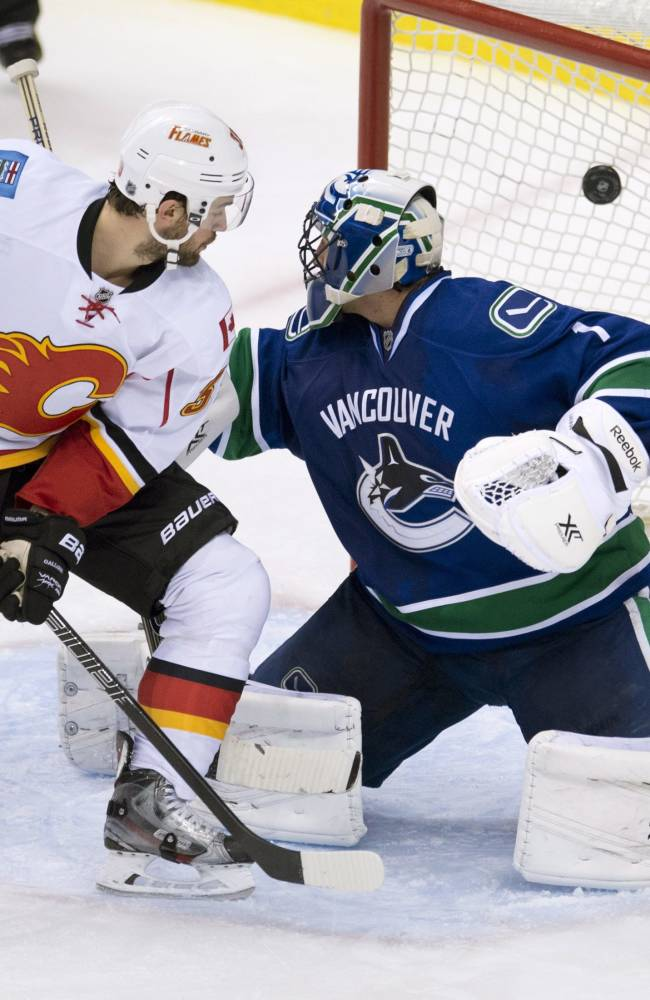 Calgary Flames left wing T.J. Galiardi (39) looks on as a shot by Calgary Flames defenseman T.J. Brodie (7) goes past Vancouver Canucks goalie Roberto Luongo (1) during the third period of NHL action in Vancouver,  British Columbia Saturday Jan. 18, 2014