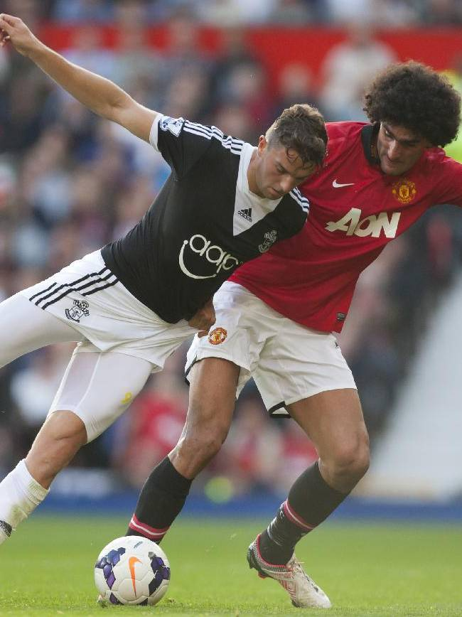Manchester United's Marouane Fellaini, right, fights for the ball against Southampton's Jay Rodriguez during their English Premier League soccer match at Old Trafford Stadium, Manchester, England, Saturday Oct. 19, 2013