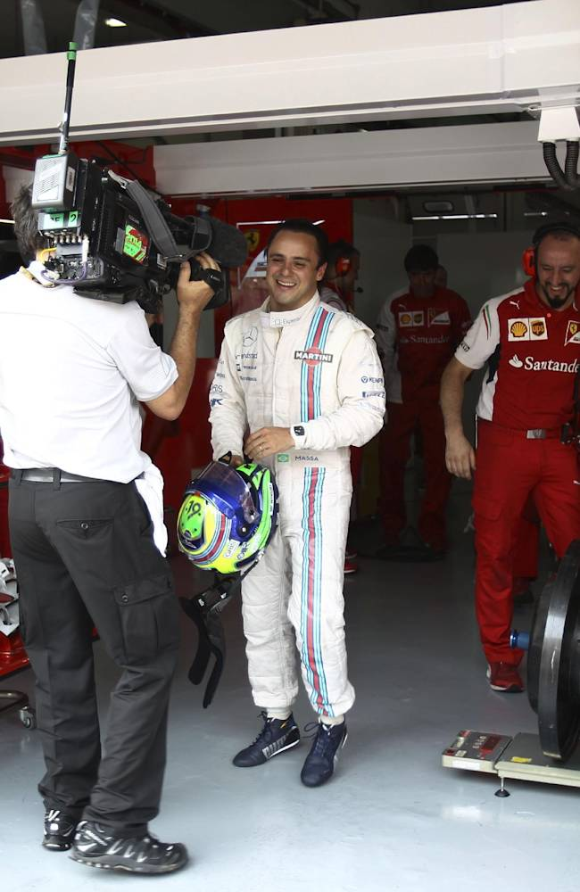 Williams driver Felipe Massa, center, of Brazil walks out from Ferrari's garage after the second practice session ahead of Sunday's Malaysian Formula One Grand Prix at Sepang International Circuit in Sepang, Malaysia, Friday, March 28, 2014