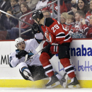 New Jersey Devils' Ryane Clowe (29) checks San Jose Sharks' Tommy Wingels (57) during the first period of an NHL hockey game Sunday, March. 2, 2014, in Newark, N.J The Associated Press