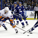 Tampa Bay Lightning right wing B.J. Crombeen (19) strips the puck from New York Islanders defenseman Matt Donovan (46) as Lightning's Nate Thompson (44), Ryan Malone (12) and Eric Brewer (2) give chase during the first period of an NHL hockey game Thursda