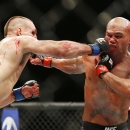 Rory MacDonald hits Robbie Lawler in their welterweight title mixed martial arts bout at UFC 189 on Saturday, July 11, 2015, in Las Vegas. (AP Photo/John Locher)