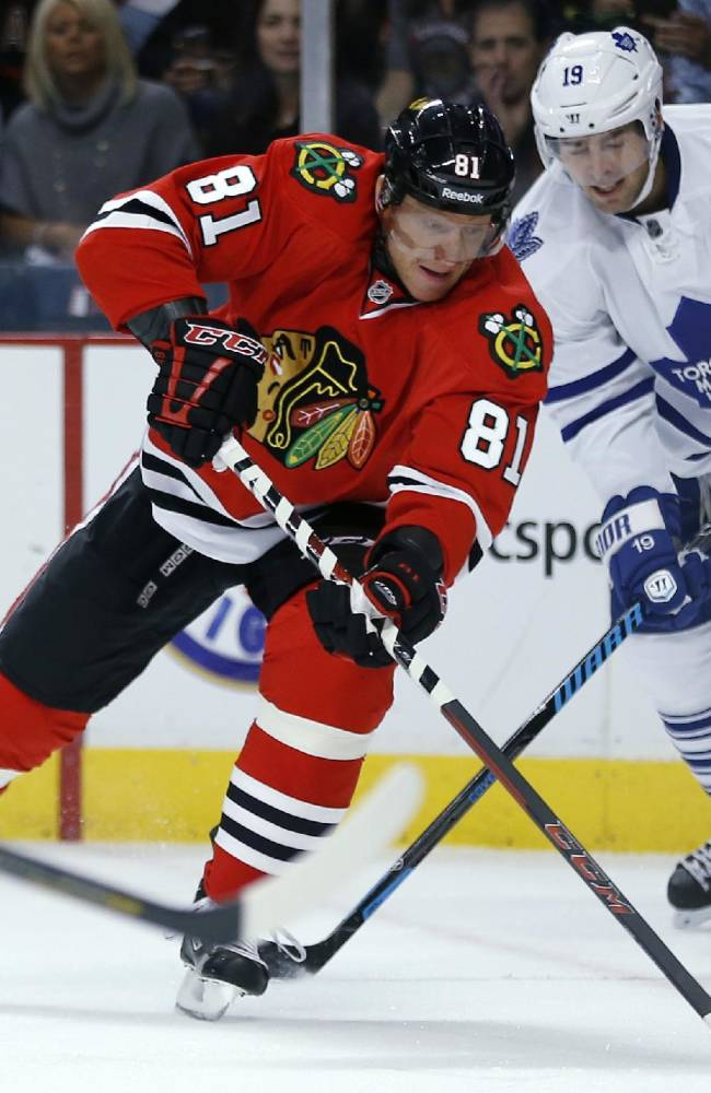 Chicago Blackhawks right wing Marian Hossa (81) advances past Toronto Maple Leafs left wing Joffrey Lupul (19) during the first period of an NHL hockey game Saturday, Oct. 19, 2013, in Chicago