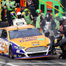 Joey Logano's crew works on his car after he crashed into the wall during the NASCAR Sprint Cup Series auto race at New Hampshire Motor Speedway on Sunday, July 13, 2014, in Loudon, N.H. The crash took Logano out of the race. Brad Keselowski won. (AP Photo/Jim Cole)