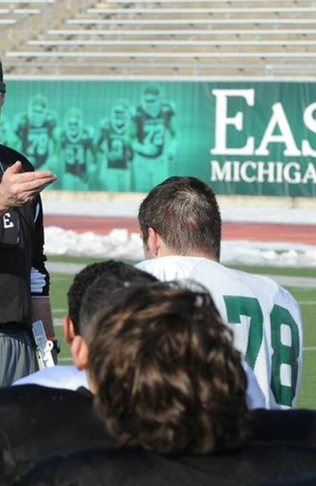 In an undated photo provided by Eastern Michigan University, head football coach Chris Creighton talks to his team in Ypsilanti, Mich. The new football coach wants his team to have the attitude that it will play anyone, anywhere. Creighton says the Eagles are so tough they would play on a parking lot