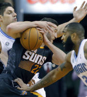 Orlando Magic forward Nikola Vucevic, of Monternegro, rear, and teammate Kyle O'Quinn (2) defend as Phoenix Suns forward Miles Plumlee drives during the first half of an NBA basketball game, Wednesday, March 19, 2014, in Phoenix. (AP Photo/Matt York)