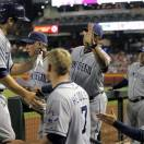 San Diego Padres' Carlos Quentin, left, is greeted in the dugout after scoring on a single by teammate Yonder Alonso during the third inning of a baseball game against the Arizona Diamondbacks, Saturday, May 25, 2013, in Phoenix.  (AP Photo/Matt York)