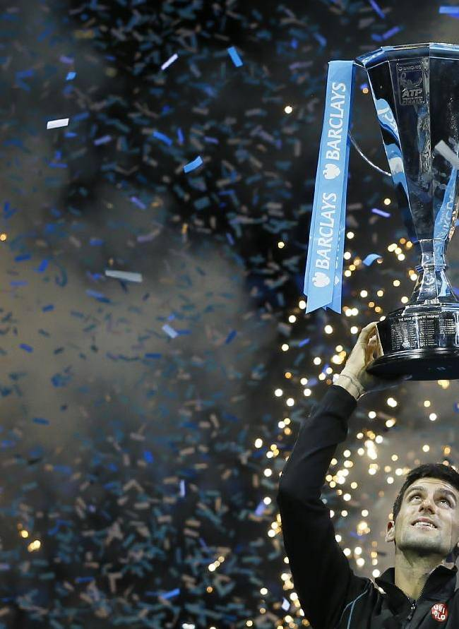 Novak Djokovic of Serbia holds up the ATP World Tour Finals tennis trophy as he poses for photographers after defeating Rafael Nadal of Spain at the O2 Arena in London, Monday, Nov. 11, 2013