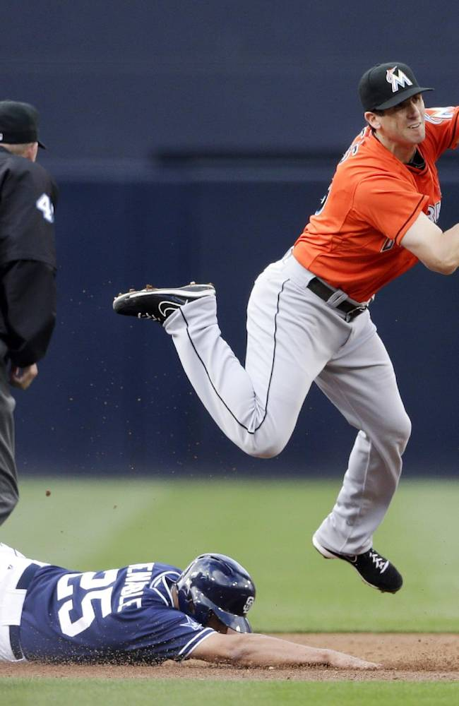 Miami Marlins third baseman Ed Lucas, right, leaps over San Diego Padres' Will Venable after getting the out on Venable during the first inning of a baseball game Saturday, May 10, 2014, in San Diego
