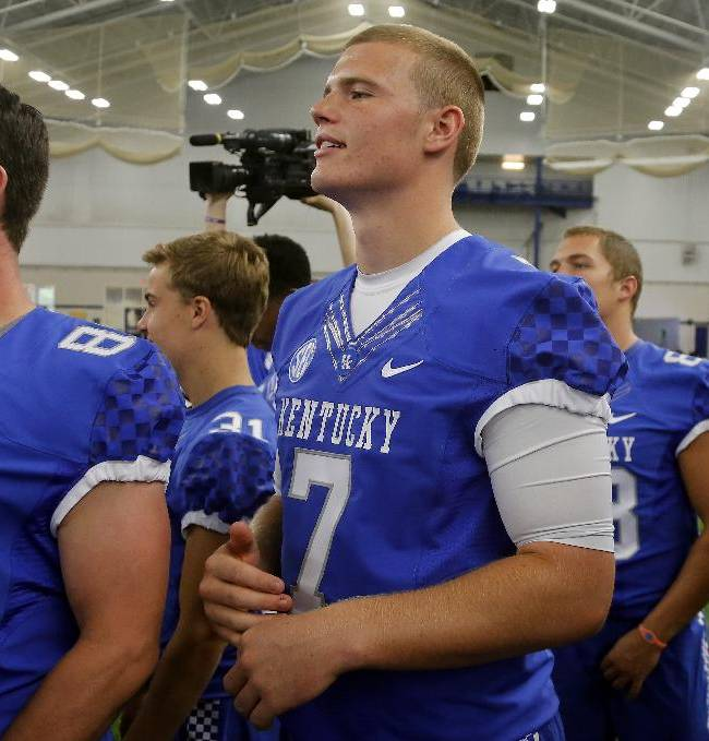 Kentucky's Drew Barker (7) watches as teammates are photographed during the team's NCAA college football media day, Friday, Aug. 8, 2014, in Lexington, Ky