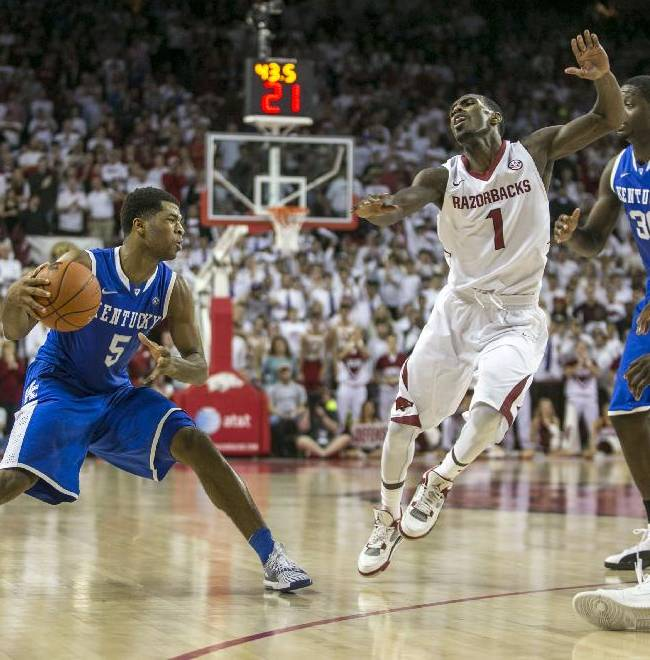 Kentucky guard Andrew Harrison, (5), recovers from a faked shot as Arkansas guard Mardracus Wade, (1), attempts a block during the second half of an NCAA college basketball game on Tuesday, Jan. 14, 2014, in Fayetteville, Ark