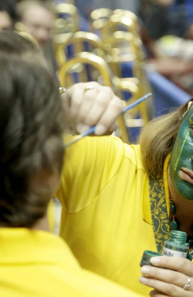 Baylor Band member Shannon Blankenbeker, right, applies face paint to another band member, Colin Gergg, prior to a regional semifinal NCAA college basketball tournament game between Baylor and Wisconsin, Thursday, March 27, 2014, in Anaheim, Calif
